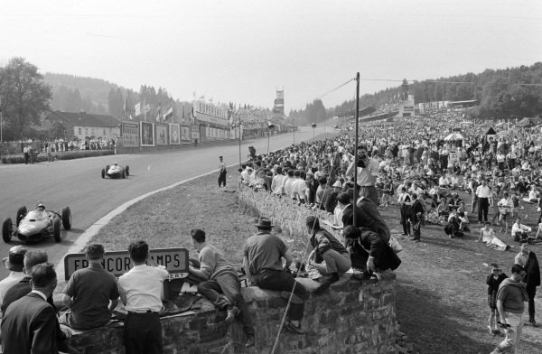 Ricardo Rodríguez, Ferrari 156, leads Phil Hill, Ferrari 156, past an excited crowd of fans.