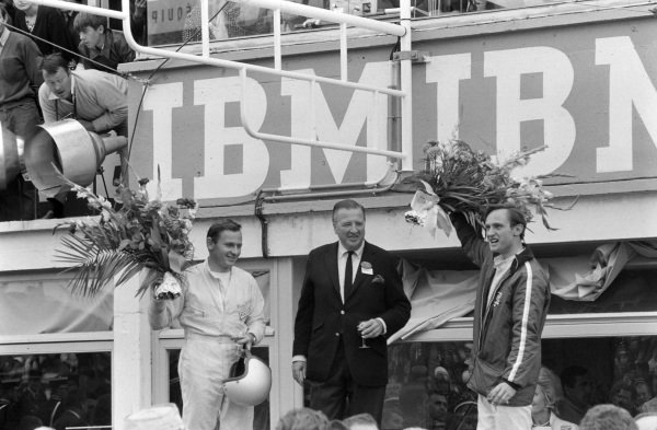 Bruce McLaren and Chris Amon, 1st position, flank Henry Ford II on the podium.