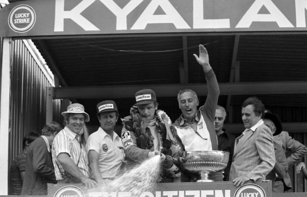 Niki Lauda, 1st position, sprays champagne on the podium.