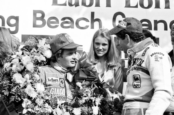 (L to R): Race winner Gilles Villeneuve (CDN) celebrates on the podium with his second placed Ferrari team mate Jody Scheckter (RSA).