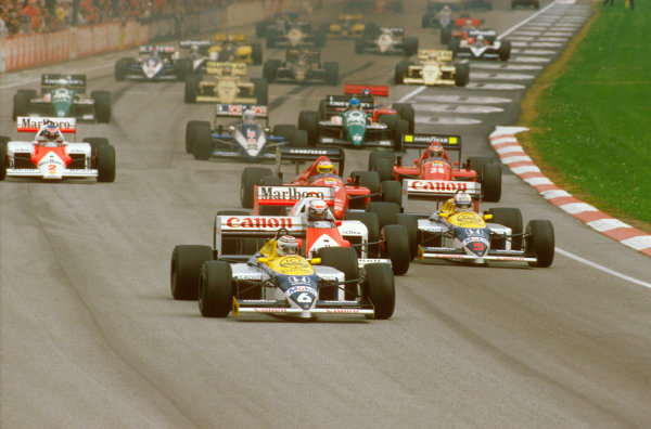 Imola, Italy.25-27 April 1986.Nelson Piquet (Williams FW11 Honda) leads Alain Prost (McLaren MP4/2C TAG Porsche), Nigel Mansell (Williams FW11 Honda), Michele Alboreto and Gerhard Berger (both Ferrari F186's) at the start.Ref-86 SM 13.World Copyright - LAT Photographic