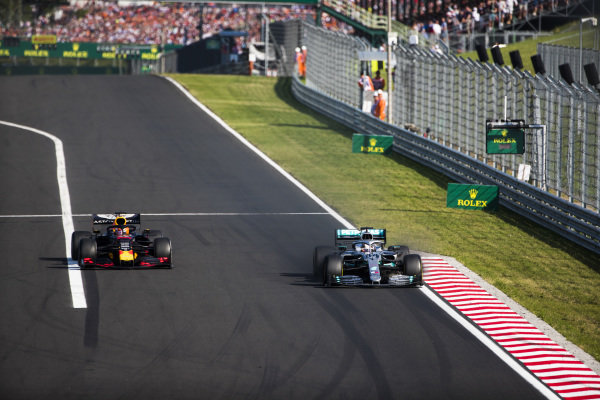 Lewis Hamilton, Mercedes AMG F1 W10, passes Max Verstappen, Red Bull Racing RB15, for the lead