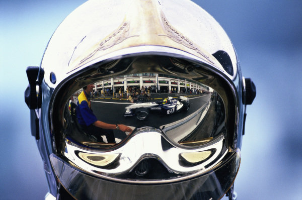 Ralf Schumacher, Williams FW25 BMW, reflected in the visor of a fire marshal.