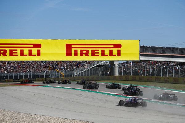 Charles Leclerc, Ferrari SF90, leads Daniel Ricciardo, Renault R.S.19, Lando Norris, McLaren MCL34, and the remainder of the field as Lance Stroll, Racing Point RP19, runs wide
