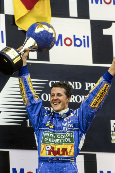 Michael Schumacher, 1st position, celebrates on the podium with his trophy.