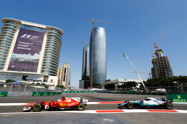 Baku City Circuit, Baku, Azerbaijan. Friday 23 June 2017. Sebastian Vettel, Ferrari SF70H, and Valtteri Bottas, Mercedes F1 W08 EQ Power+, exit the pit lane. World Copyright: Steven Tee/LAT Images ref: Digital Image _O3I0895