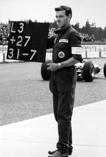 1965 German Grand Prix.Nurburgring, Germany. 1 August 1965.A Lotus mechanic holds out the lap board for eventual winner, Jim Clark, Lotus 33, portrait.World Copyright: LAT PhotographicRef: B/W Print