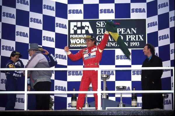 Ayrton Senna, 1st position, with the Brazilian flag on the podium.  Tom Wheatcroft congratulates Alain Prost, 3rd position, on the left of frame.