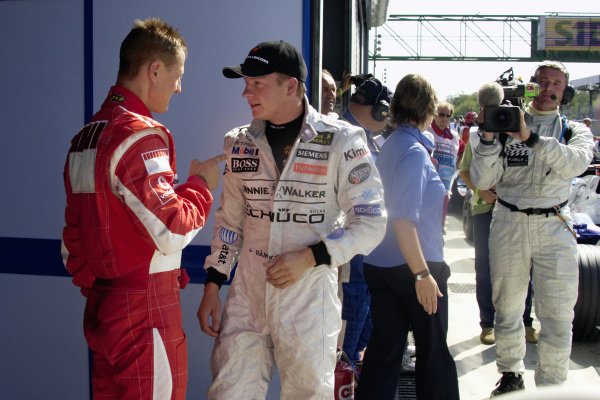 Michael Schumacher and Kimi Räikkönen chat in parc fermé after qualifying.