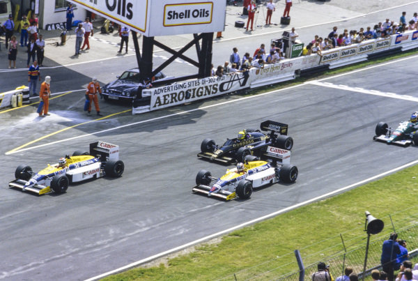 Nelson Piquet, Williams FW11 Honda, leads Nigel Mansell, Williams FW11 Honda, and Ayrton Senna, Lotus 98T Renault, at the start.