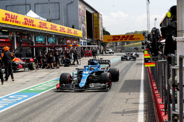 Fernando Alonso, Alpine A521, leads Pierre Gasly, AlphaTauri AT02, in the pit lane