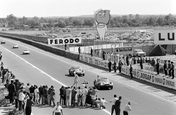 Olivier Gendebien / Phil Hill, SpA Ferrari SEFAC, Ferrari 330 TRI/LM (Spyder), raises his arm as he crosses the line and takes the chequered flag ahead of Pierre Noblet / Jean Guichet, Ferrari 250 GTO.