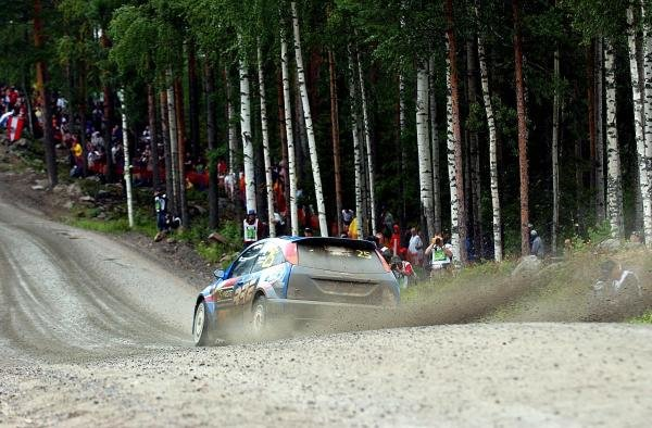 A camera man gets covered in dirt and stones as the number 25 Ford Focus WRC passes.FIA World Rally Championship, Rd9, Neste Rally Finland, Jyvaskyla, Finland. Day 2, 9 August 2003.DIGITAL IMAGE