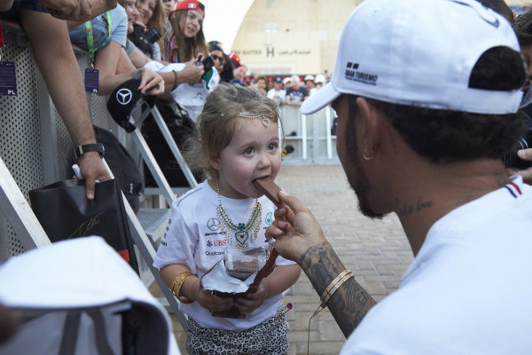 Lewis Hamilton, Mercedes AMG F1, shares a biscuit with a small fan