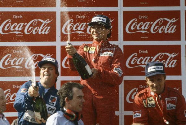 Michele Alboreto, 1st position, celebrates by spraying champagne on the podium, alongside Derek Warwick, 2nd position, and René Arnoux, 3rd position.