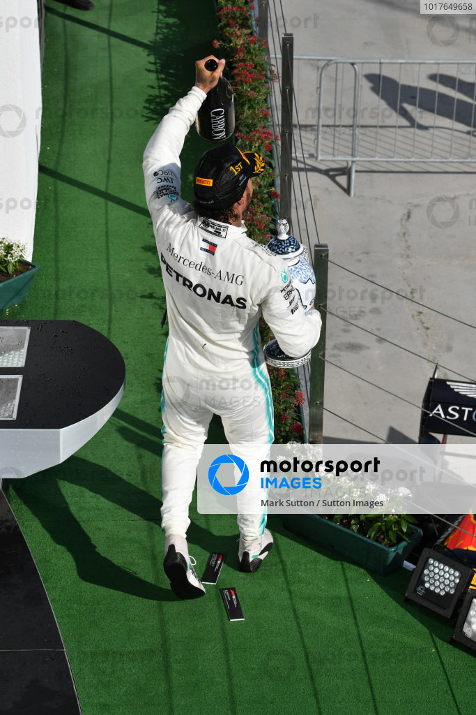 Lewis Hamilton, Mercedes AMG F1, 1st position, leaves the podium with his trophy and Champagne