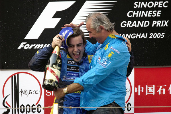 Fernando Alonso celebrates victory and the constructors' championship title on the podium with Flavio Briatore.