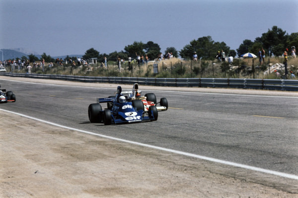 Emerson Fittipaldi, McLaren M23 Ford coming up alongside Jody Scheckter, Tyrrell 007 Ford.