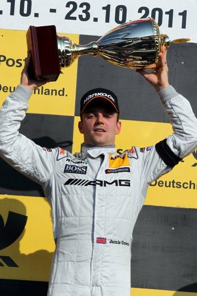 Race winner Jamie Green (GBR), AMG Mercedes, celebrates with his trophy on the podium.DTM, Rd10, Hockenheim, Germany, 22-23 October 2011 World Copyright: LAT Photographicref: Digital Image dne1123oc78