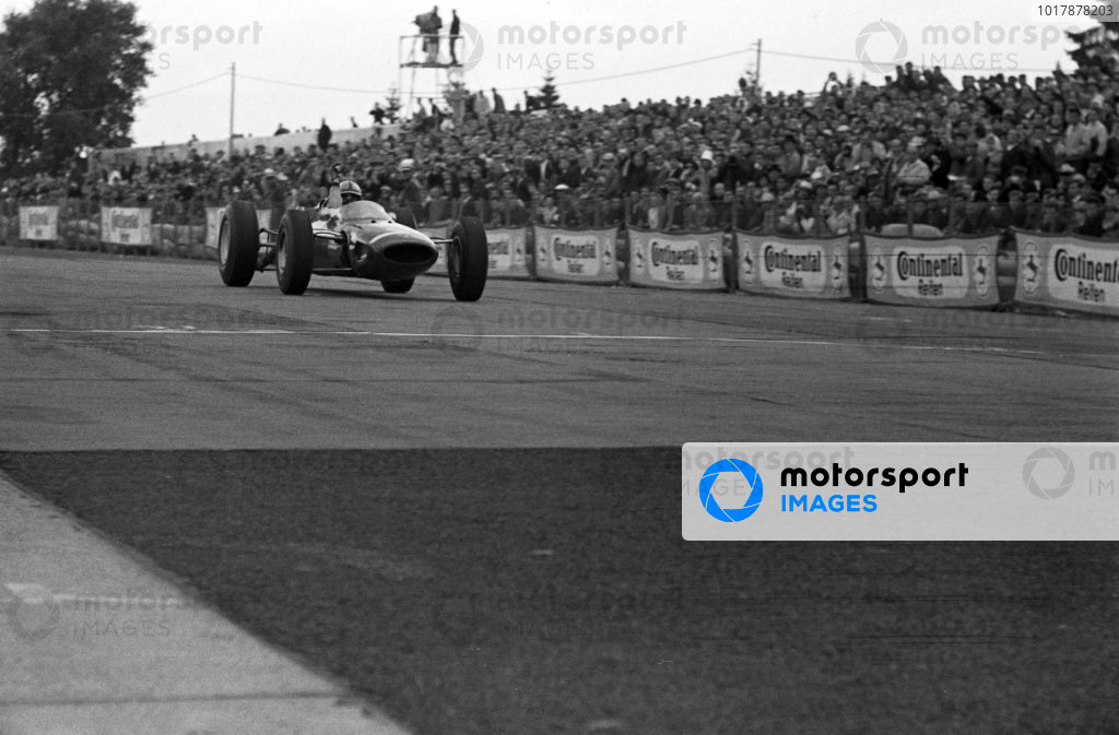 John Surtees, Ferrari 158, celebrates as he crosses the finish line for victory.