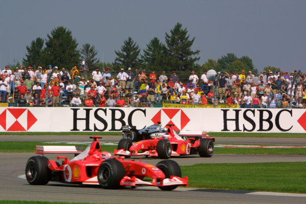 2002 American Grand Prix.Indianapolis, Indiana, USA. 27-29 September 2002.Michael Schumacher followed by Rubens Barrichello (both Ferrari F2002's) and David Coulthard (McLaren MP4/17 Mercedes). They finished in 2nd, 1st and 3rd positions respectively.World Copyright - LAT Photographicref: Digital File Only