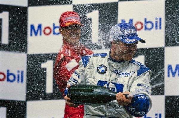 Ralf Schumacher, 1st position, celebrates on the podium with Michael Schumacher, 3rd position.