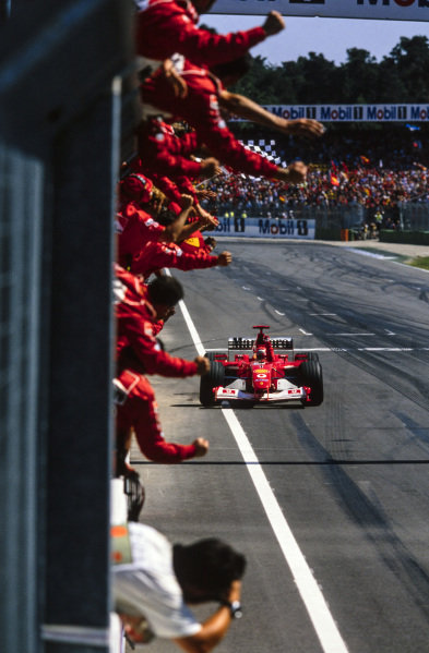 Michael Schumacher, Ferrari F2002, celebrates with the team as he crosses the finish line and takes the chequered flag.