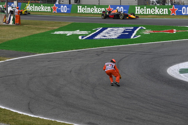 A marshal clears debris from the track