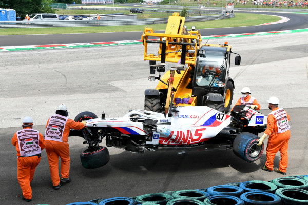 Marshals remove the damaged car of Mick Schumacher, Haas VF-21, from a tyre barrier after his crash in FP3