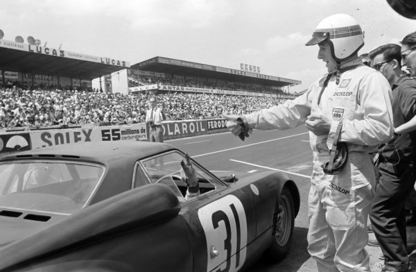 Jackie Stewart gives a thumbs up to Graham Hill whoi returns with his own gesture as he drives their Owen Racing Organisation, Rover-BRM, out of the pits.