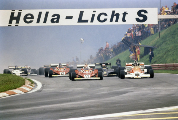 Pole sitter Niki Lauda, Ferrari 312T2 leads the field at the start with James Hunt, McLaren M26 Ford alongside.