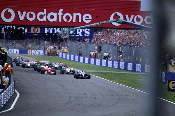 Kimi Räikkönen, McLaren MP4-19B Mercedes leads Rubens Barrichello, Ferrari F2004 and Jenson Button, BAR 006 Honda at the start.