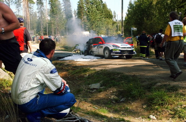 Colin McRae (GBR) watches his Ford Focus RS WRC burn after a loose hyrdaulic cable caught fire.FIA World Rally Championship, Rd9, Neste Rally Finland, Day Three, Finland. 11 August 2002.DIGITAL IMAGE