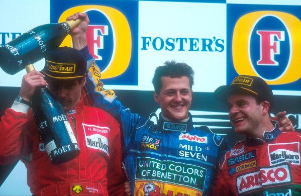 1994 Pacific Grand Prix.Tanaka International, Aida, Japan.15-17 April 1994.Michael Schumacher (Benetton Ford) celebrates his 1st position with Gerhard Berger (Ferrari) 2nd position and Rubens Barrichello (Jordan Hart) 3rd position on the podium.Ref-94 PAC 27.World Copyright - LAT Photographic