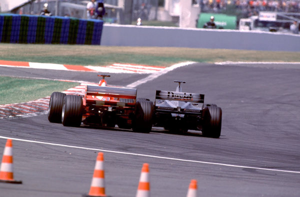 2000 French Grand Prix.Magny-Cours, France. 30/6-2/7 2000.David Coulthard (McLaren MP4/15 Mercedes) touches wheels with Michael Schumacher (Ferrari F1-2000) as he goes down the inside at the Hairpin, to overtake for the lead.World Copyright - LAT PhotographicFormat: 35mm transparency
