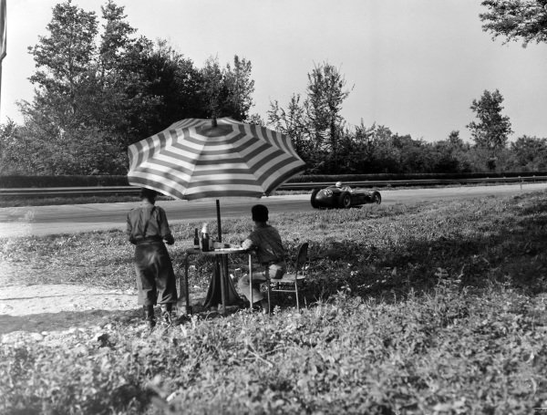 Fans enjoy some refreshment as they watch Carroll Shelby, Aston Martin DBR4/250, go past.