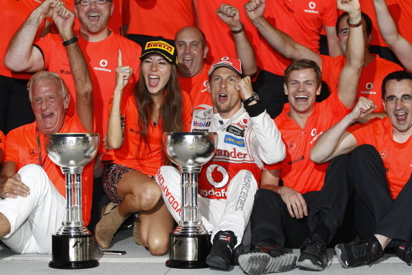 Jenson Button celebrates victory with the McLaren team, his father John and his girlfriend Jessica Michibata.