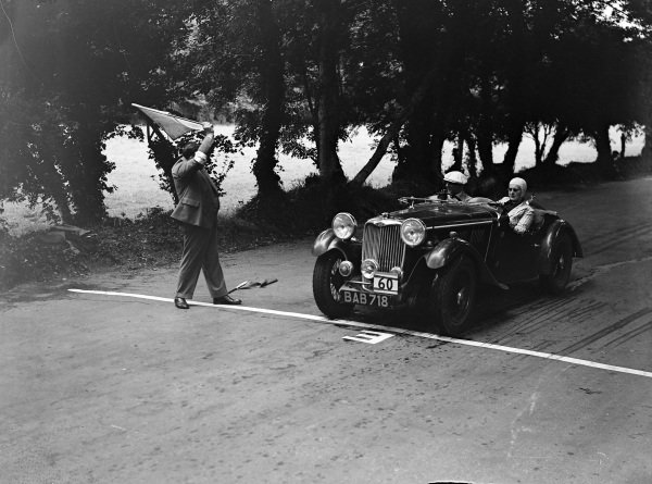 F. S. Barnes, Singer, passes an official waving a flag.