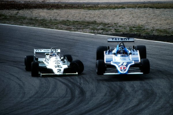 Carlos Reutemann (ARG), Williams FW07C, attempts to overtake Jacques Laffite (FRA), Ligier JS17, on lap 18. Reutemann then crashed into the side of Laffite briefly launching him into the air and then into the catch-fencing. Reutemann retired with broken suspension.