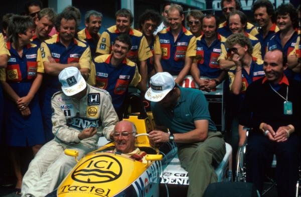 BBC TV commentator Murray Walker (GBR) in the Williams FW11 is teased by the regular drivers Nelson Piquet (BRA) (left) and Nigel Mansell (GBR) (right). Team Owner Frank Williams (GBR) (right) enjoys the prank. Portugese Grand Prix, Estoril, 21 Septmeber 1986.