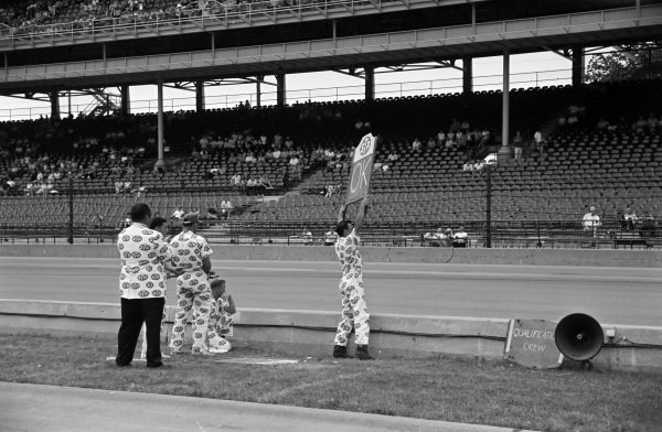 A pit board is held out for Bobby Unser, Andy Granatelli, Ferguson Novi.