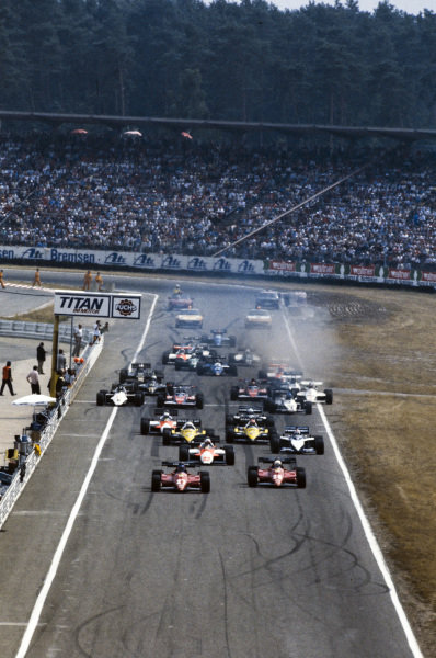Patrick Tambay, Ferrari 126C3, and team mate René Arnoux, Ferrari 126C3, lead the field at the start. Behind them are Andrea de Cesaris, Alfa Romeo 183T, Nelson Piquet, Brabham BT52B BMW, Alain Prost, Renault RE40, Eddie Cheever, Renault RE40, Mauro Baldi, Alfa Romeo 183T, and Riccardo Patrese, Brabham BT52B BMW. Further back, Thierry Boutsen, Arrows A6 Ford, is forced onto the grass.
