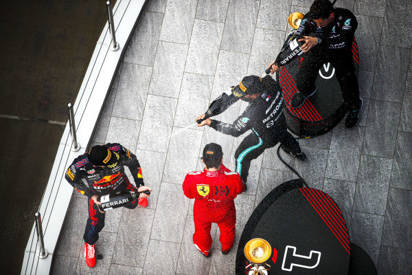 Max Verstappen, Red Bull Racing, 2nd position, Carlos Sainz, Ferrari, 3rd position, the Mercedes team representative and Sir Lewis Hamilton, Mercedes, 1st position, spray Champagne on the podium