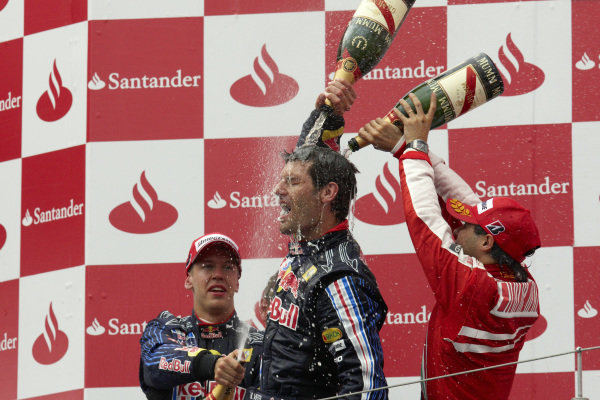 Mark Webber celebrates his first victory with teammate Sebastian Vettel, 2nd position, and Felipe Massa, 3rd position.