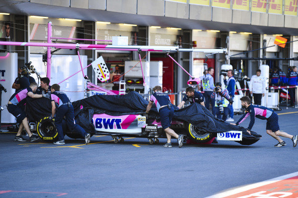 Racing Point mechanics return the damaged car of Lance Stroll, Racing Point RP19, to the garage, under a sheet