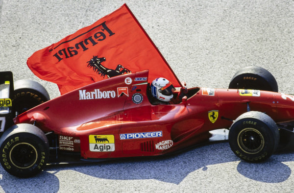 Nicola Larini, Ferrari 412T1, drives with a Ferrari flag after finishing in second place.
