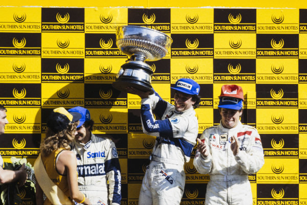 Riccardo Patrese, 1st position, lifts his trophy on the podium. Andrea de Cesaris, 2nd position, and Nelson Piquet, 3rd position, are alongside.