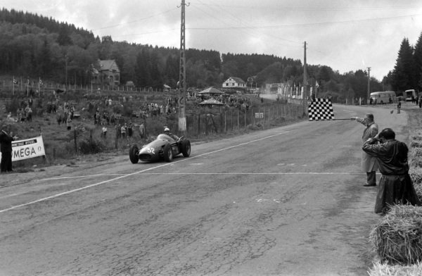 Jean Behra, Maserati 250F, takes the chequered flag.