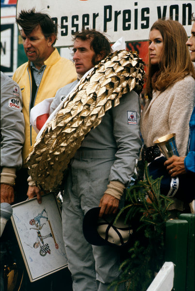 1973 German Grand Prix.  Nurburgring, Germany. 3-5th August 1973.  Jackie Stewart, Tyrrell, 1st position, on the podium with wife Helen, team boss Ken Tyrrell, and a signed, framed cartoon.  Ref: 73GER08. World Copyright: LAT Photographic