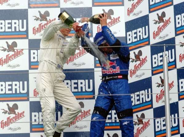 (L-R) Alexander Margaritis (GRE) Weigl Motorsport 2nd (later disqualified) celebrates with champagne on the podium with race winner Christian Klien (AUT) JD Motorsport.German Formula Renault Championship, Rd6, Races 11 and 12, Nurburgring, Germany. 22 September 2002.DIGITAL IMAGE
